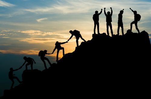 An image of a team of people reaching the peak of a mountain